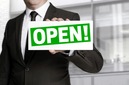 openly: Businessman holding open sign to viewer.