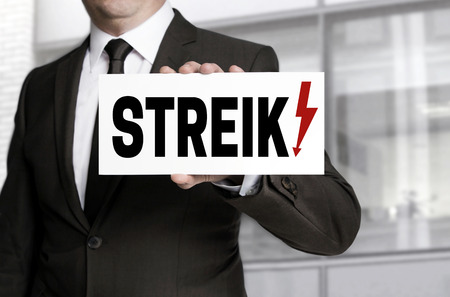 collective bargaining: Businessman holding sign strike to viewer. Stock Photo
