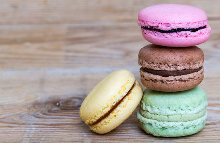 Colorful macarons on rustic wood.
