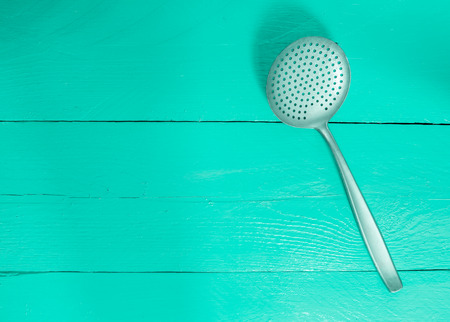 slotted: slotted spoon on turquoise wood as a background.