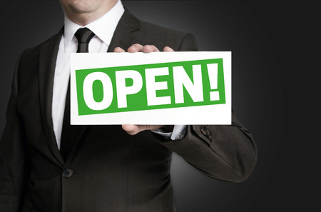 openly: Open sign is held by businessman.