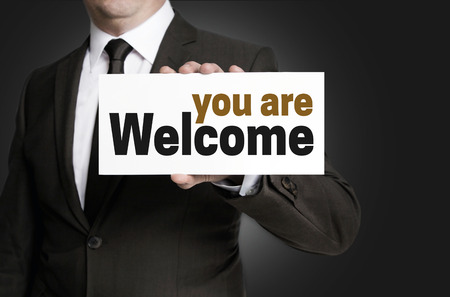 shield sign: Welcome sign is held by businessman.