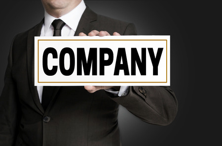Company sign is held by businessman.