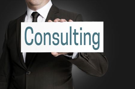 consulting sign is held by businessman. Stock Photo