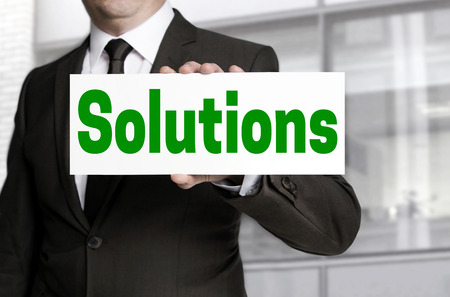 Solutions sign is held by businessman.