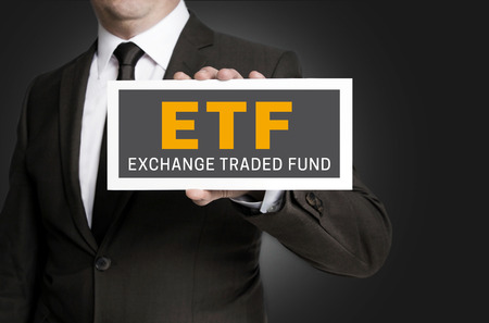 traded: ETF sign is held by businessman.