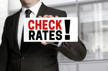 rates: Check Rates sign is held by businessman. Stock Photo
