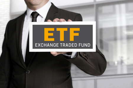 traded: ETF sign is held by businessman background.