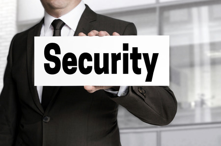 elementos de protecci�n personal: Security sign is held by businessman.