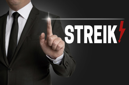 collective bargaining: streik touchscreen is operated by businessman concept.