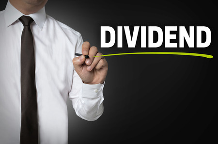 dividend: Dividend is written by businessman background concept. Stock Photo