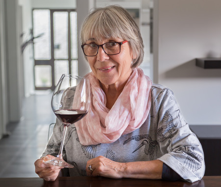 lady in red: Senior woman drinking wine at a table. Stock Photo