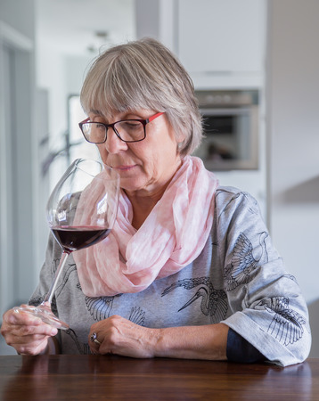 critic: Senior woman drinking wine at a table. Stock Photo