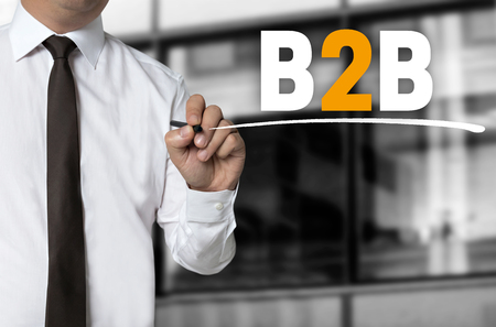 b2b: B2B is written by businessman background concept. Stock Photo