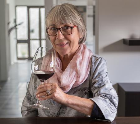 bebiendo vino: Mujer mayor que bebe el vino en una mesa. Foto de archivo