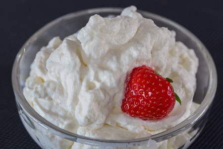 glass bowl: Cream with strawberry in a glass bowl.