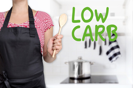 minimization: low carb cook holding wooden spoon background concept.