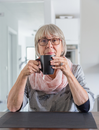 looking at viewer: Senior woman holding teacup, looking toward the viewer.