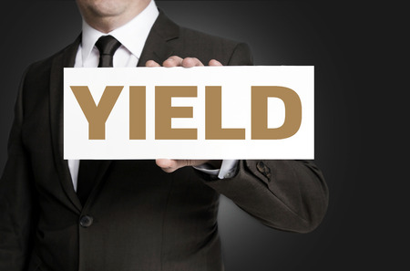 yield sign: yield sign held by businessman concept.