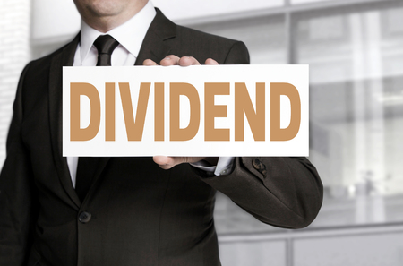dividend: dividend sign is held by businessman concept.