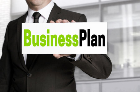 businessplan: Business Plan sign is held by businessman concept.