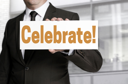 celebrate: celebrate sign is held by businessman concept.