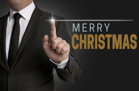 touchscreen: Merry Christmas touchscreen operated by businessman concept.
