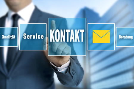 touchscreen: Contact (in german language Kontakt) touchscreen is operated by businessman.