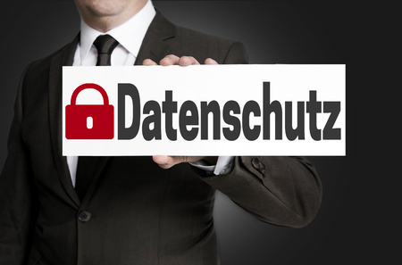 security symbol: data protection (in german datenschutz) placard is held by businessman.
