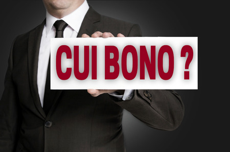 bono: cui bono sign is held by businessman background.