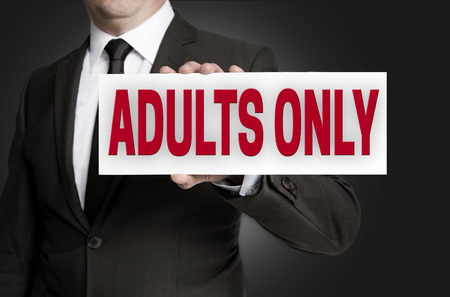 adults only sign held by businessman background.