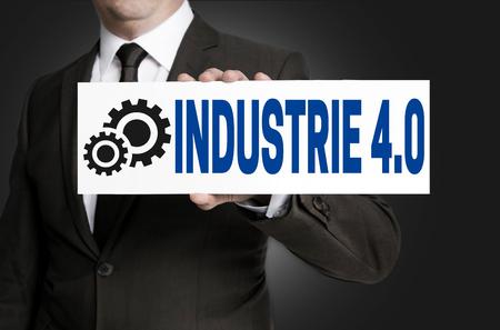 industrie: industrie 4.0 in german industry sign is held by businessman.