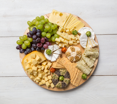 cheese plate: Cheese plate variation on a wooden white table.