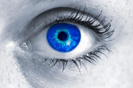 ultramarine blue: Eye with blue iris looks at viewer concept macro.