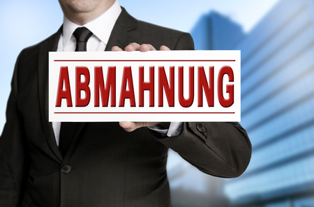 admonition: abmahnung (in german warning) sign is held by businessman.