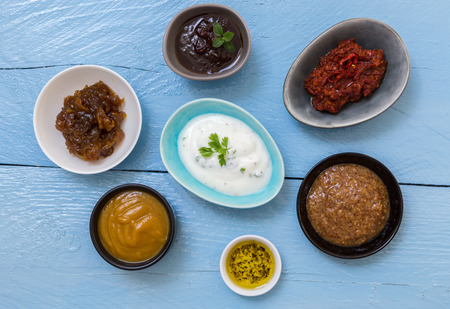 sauces: Variation of sauces and dips on wood background. Stock Photo