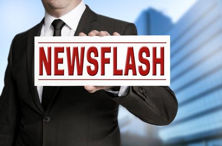 newsflash: newsflash sign is held by businessman.