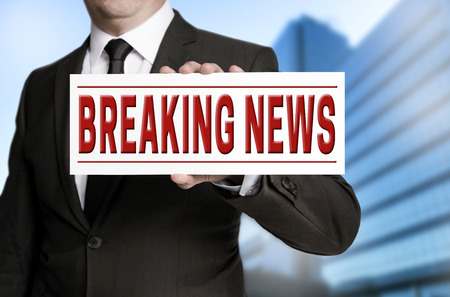 newsflash: breaking news sign is held by businessman.