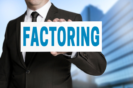 factoring sign is held by businessman.