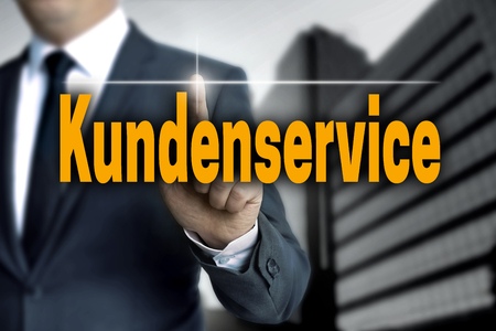 Kundenservice (in german Customer Care) touchscreen is operated by businessman. Stock Photo