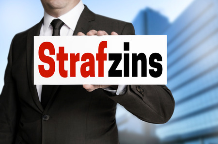 strafzins (in german negative interest) sign is held by businessman. Stock Photo