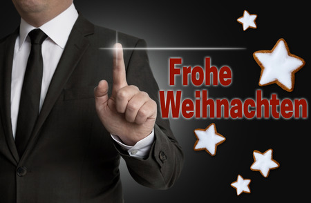 frohe: Frohe Weihnachten (in german Merry Christmas) touchscreen is operated by a businessman.