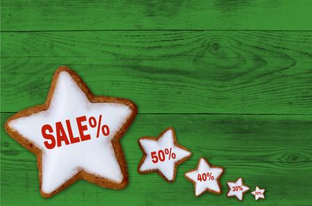Sale cinnamon star on green wood concept. Stock Photo