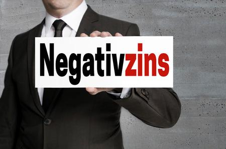 negativzins (in german negative interest) sign is held by businessman.