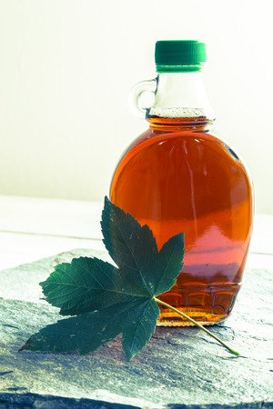 maple syrup: Maple syrup in a bottle with maple leaf.