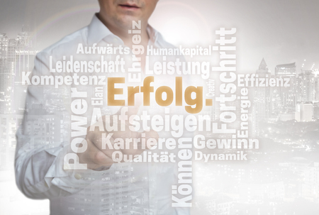 Erfolg Wordcloud (in german success) touchscreen is operated by man.