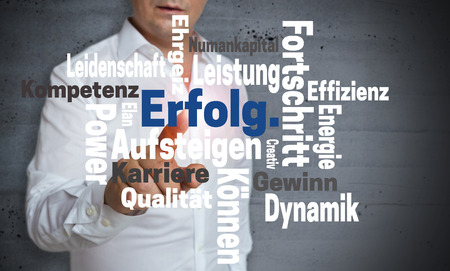 Erfolg (in german Success) Wordcloud touchscreen is operated by man. Stock Photo