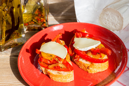 Bruschetta with peppers and goat cheese on a wooden board. Stock Photo