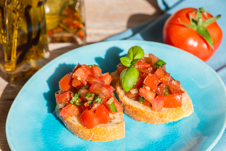 Bruschetta with tomatoes on a wooden board.
