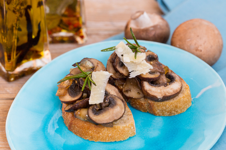 Bruschetta with mushrooms on a wooden board.